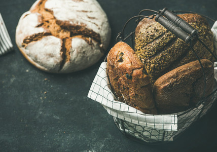 Various bread loaves over black background  copy space