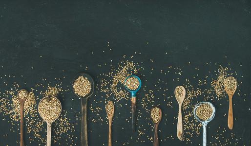 Various vintage kitchen spoons full of green buckwheat grains