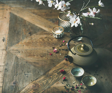 Asian golden iron teapot cups candles and almond blossom flowers