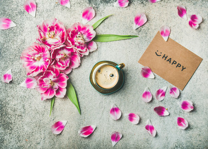 Cup of coffee surrounded with tulip flowers and sign happy