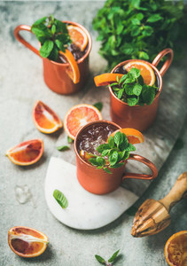 Blood orange Moscow mule alcohol cocktails over concrete background