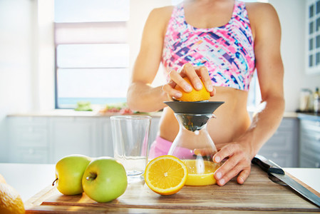 Sportive woman pressing orange juice with squeezer