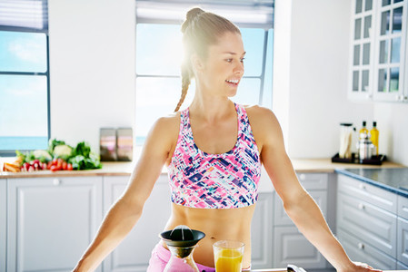 Young smiling female athlete at light kitchen