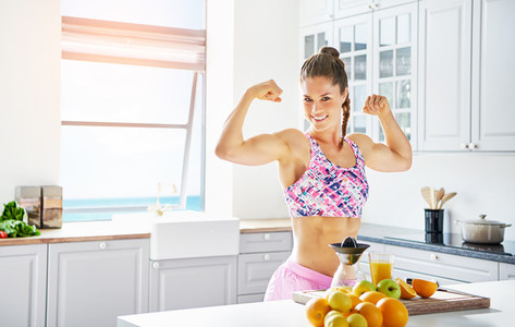 Young sportive woman smiling and showing biceps