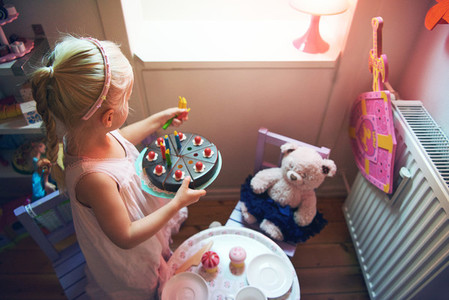 Girl holding toy cake while playing tea party