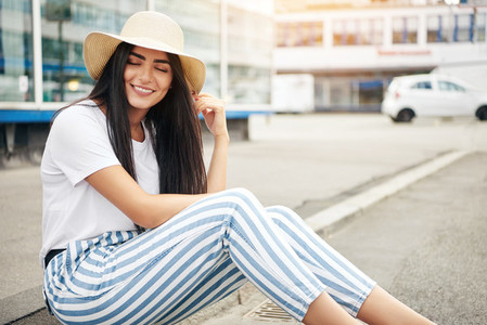 Woman in straw hat and striped pants sits on curb