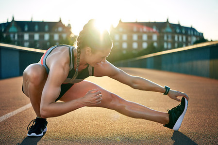 Female jogger stretches one muscular leg