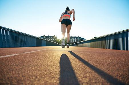 Lean athletic female runner caught mid flight