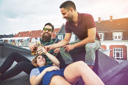Three adults enjoying beer and friendship