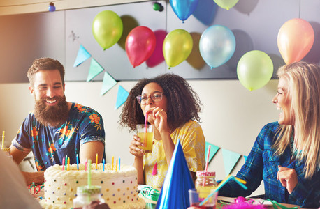 Woman sipping yellow drink near cake at party
