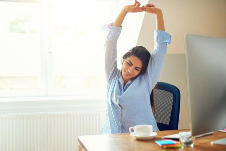 Woman stretching in front of desk at home