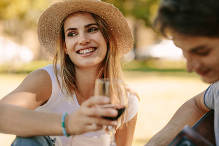 Close up of a woman sitting in park holding a wine glass