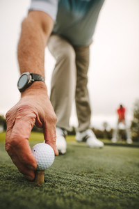 Golfer placing golf ball on tee at green