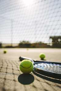 Close up of a tennis racket and balls lying on a court