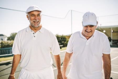 Senior men walking on a tennis court during a game of tennis