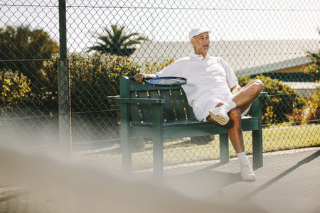 Senior man relaxing after a game of tennis