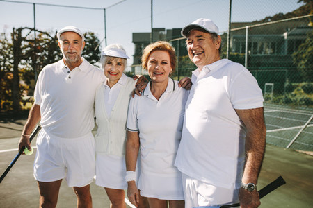 Senior couples in tennis wear standing in a tennis court