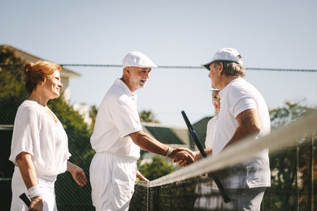 Seniors playing mixed doubles tennis game