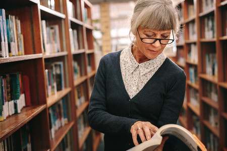 Senior woman looking at a book standing in library