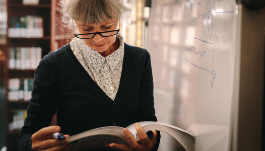 Portrait of a senior woman looking at a book in library