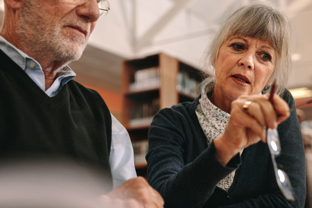 Close up of a senior couple discussing sitting in a library