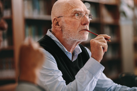 Senior man thinking deeply sitting in classroom
