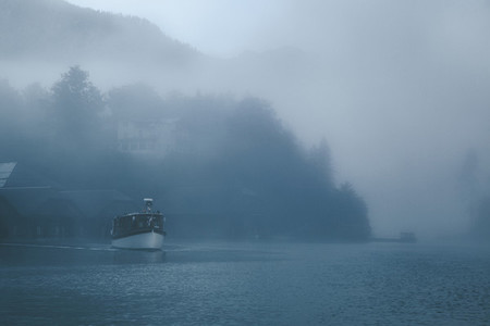 Views of lonely boat in the mist on the Konigsee lake of Germany