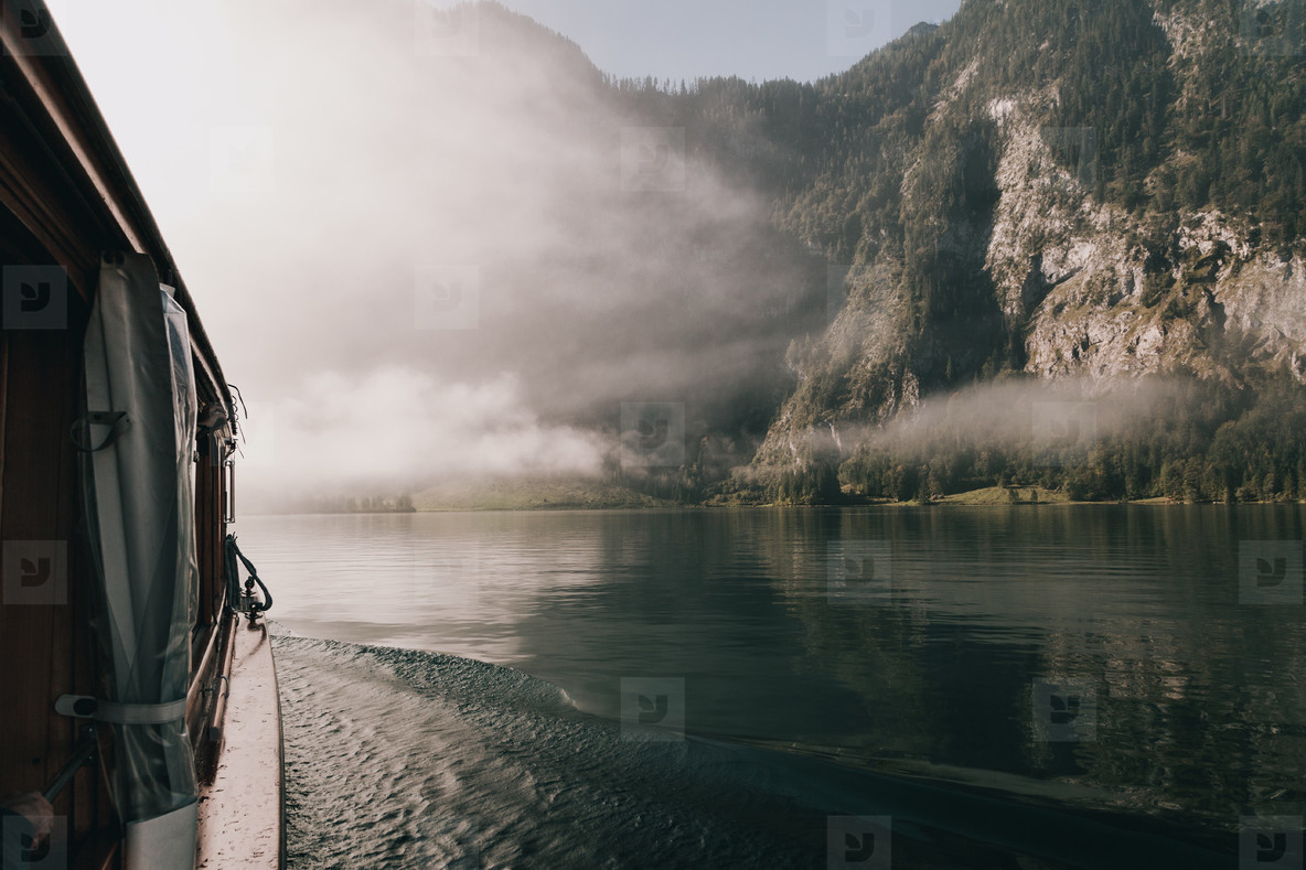views from a boat of the mountain among fog in border of the lake