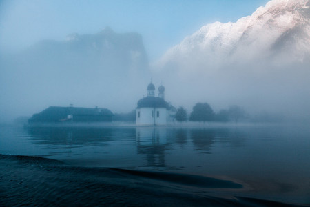 Views of St Bartholomews Church among fog in the autumn from konigsee lake