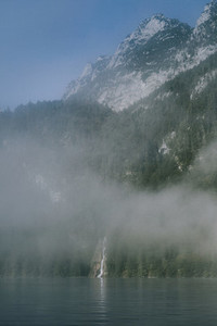 views of forest among fog in border of the lake with a waterfall