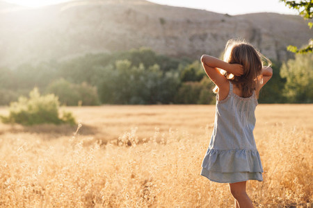 Young blonde girl playing with sunlight in the fields sunset