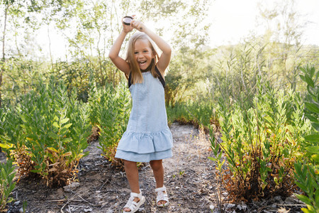 Young blonde girl running in the field wearing a dress