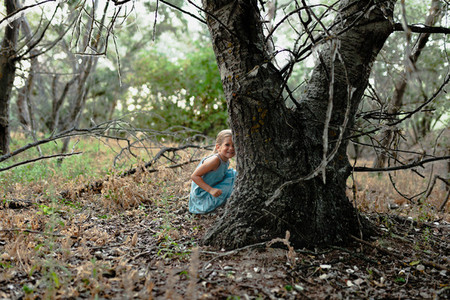 Young smile blonde girl crouched on the ground near a tree