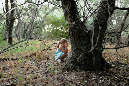 Young blonde girl crouched on the ground near a tree