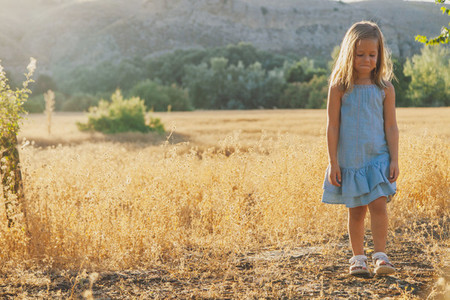 Young bored blonde girl looking at camera in the field wearing a dress