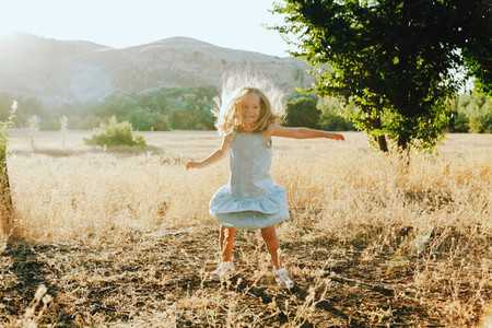 Young blonde girl jumping in the field wearing a dress