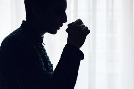Silhouette of man drinking coffe
