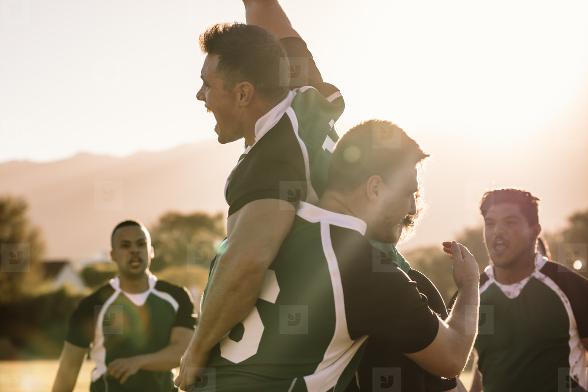 Excited rugby players celebrating a win