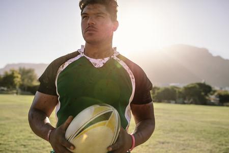Rugby player holding a ball on ground
