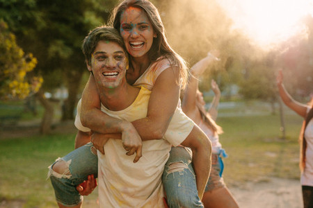 Man carrying his girlfriend on his back while playing holi