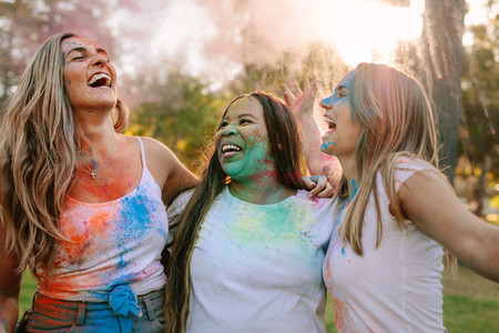 Women friends playing holi in a park