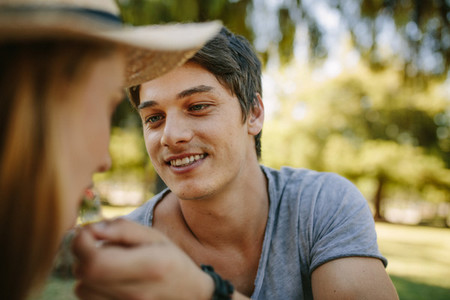 Close up of a man feeding picnic to his girlfriend