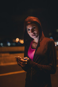 Female runner taking break after workout at night