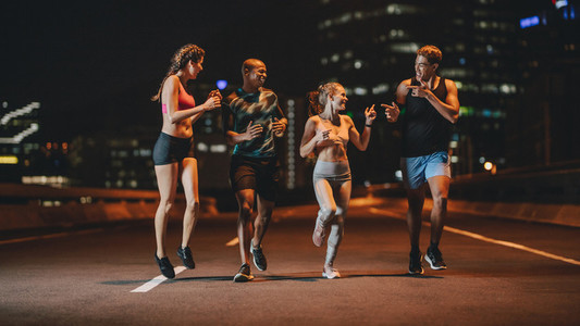 Runners training together outdoors in evening