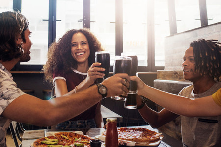 Multi ethnic group of friends toasting cold drinks at restaurant