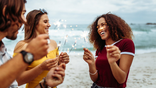 Diverse group of friends with sparklers at beach