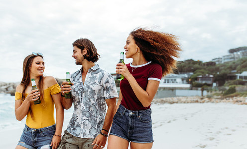 Multi ethnic friends with beers walking along the beach