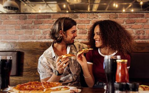 Couple enjoying eating pizza at cafe