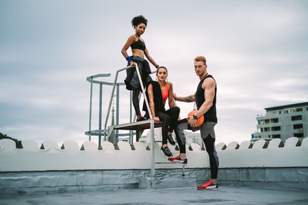 Group of athletes standing on rooftop after workout