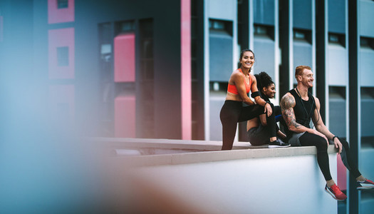 Fitness people relaxing after workout sitting on rooftop